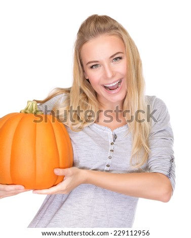 Happy smiling female holding in hands ripe orange pumpkin, isolated on white background, enjoying traditional Thanksgiving day food - stock photo