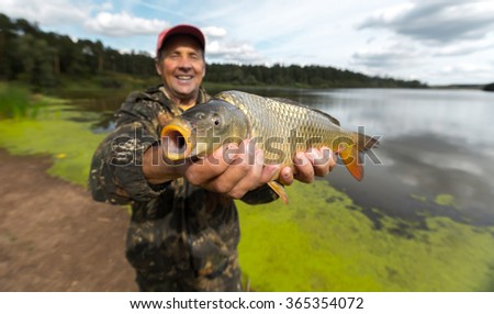 Happy smiling fisherman holding his carp (Cyprinus carpio) with lake on the background. Focus on the fish - stock photo