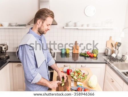 Happy smiling forty years old caucasian man chopping vegetables to make fresh salad in the kitchen. Healthy food and diet concept. - stock photo
