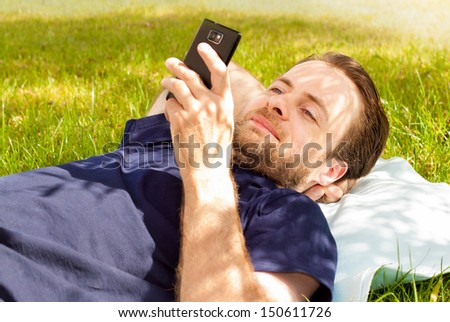 Happy smiling forty years old caucasian man looking at mobile phone while laying on grass in park during a sunny summer day - stock photo