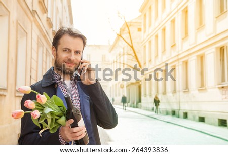Happy smiling forty years old caucasian man with wine and flower bouquet talking on a mobile phone. Street and city buildings as background. - stock photo