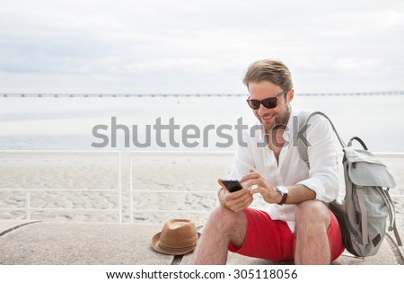 Happy smiling forty years old caucasian tourist man looking at mobile phone outdoor. Beach and sea as background - summer holiday traveling. - stock photo