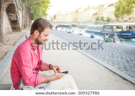 Happy smiling forty years old caucasian tourist man looking at mobile phone (smartphone) in Paris near Seine river. Summer holiday traveling. - stock photo