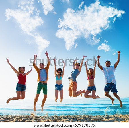 Happy smiling friends jumping over a blue sky with a world map made of clouds