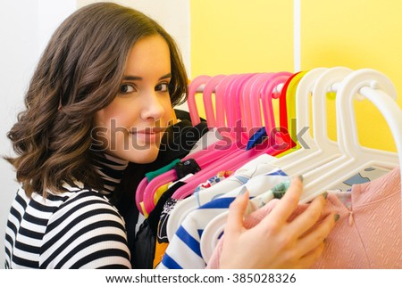 Happy smiling girl hugging her clothes on the hanger. - stock photo