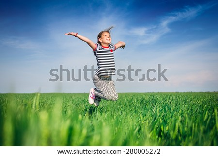 Happy smiling girl jumping at the field of wheat - stock photo