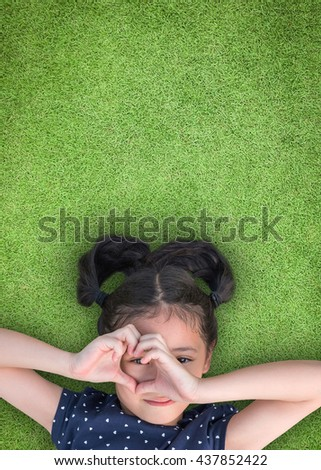 Happy smiling girl kid lying on green grass lawn looking through heart love shape hand hole: National children's eye health and safety month in August Child's eyesight healthcare awareness CSR concept - stock photo