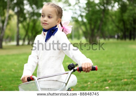 Happy smiling girl on a bicycle in the green park - stock photo