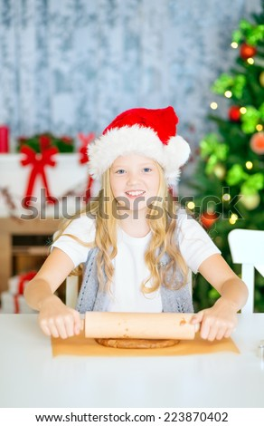 Happy smiling girl rolling dough for christmas cookies at home, with Christmas Hat, Decorated Christmas Tree and chimney at background. - stock photo