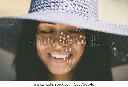 Happy smiling girl wearing a blue hat on the sea beach - stock photo