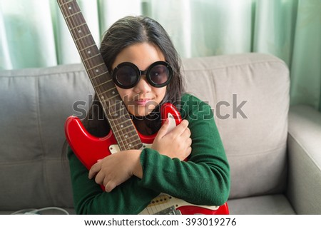 Happy smiling girl ,wearing glasses,learning to play the Electric guitar at home laying on sofa  - stock photo