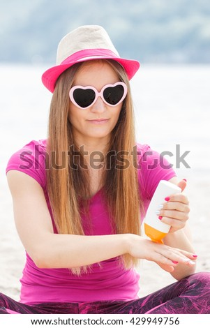 Happy smiling girl wearing straw hat and sunglasses in shape of heart on seaside and using sun lotion, sun protection on beach - stock photo