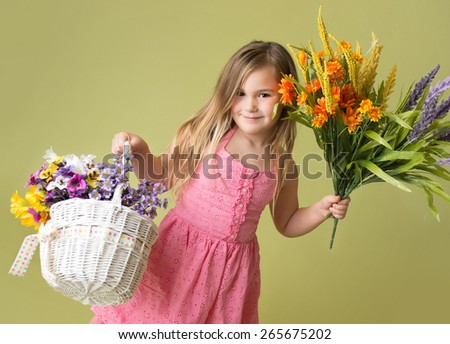 Happy smiling girl with a bunch of spring flowers in a basket looking at the camera, green background - stock photo