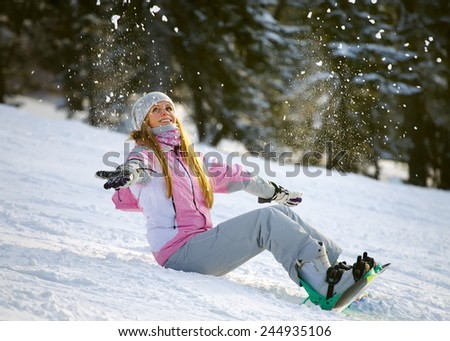Happy smiling girl with lifted hands on snowboard about to slide downhill the mountain - stock photo