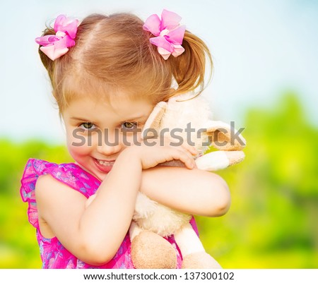 Happy smiling girl with lovely soft toy in the garden in daycare, having fun outdoors, spring season, happy childhood concept - stock photo