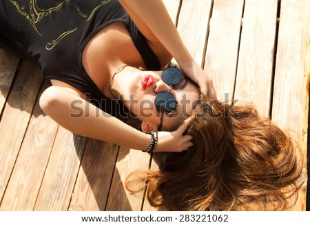 Happy smiling girls on the beach,woman funky happy and colorful wearing sunglasses and laying on the beach and send a kiss,having summer fun during travel holidays vacation.traveling,summertime - stock photo
