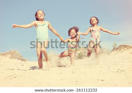 Happy Smiling girls running down the dunes at the beach. Vintage Instagram effect - stock photo