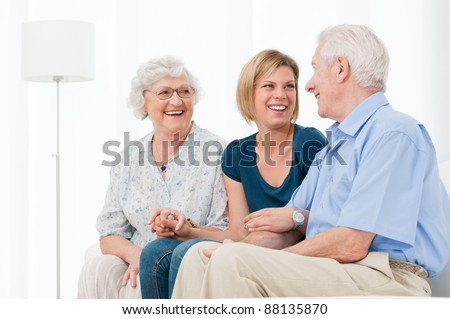 Happy smiling granddaughter enjoy the time with her grandparents at home - stock photo