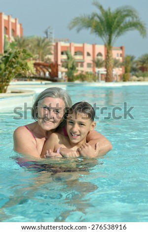 Happy smiling grandma and grandson in blue pool water