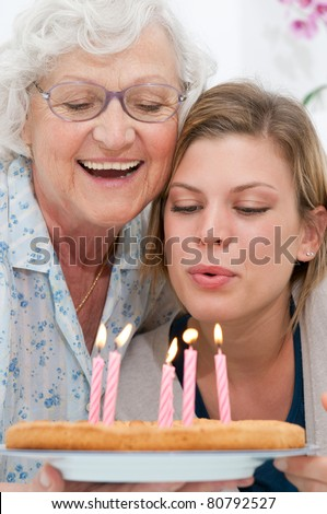 Happy smiling grandmother celebrating and giving a birthday cake to her grandson at home - stock photo