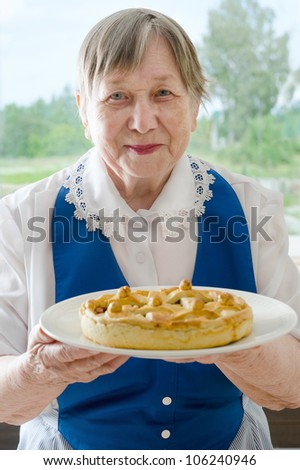 Happy smiling grandmother  showing her apple pie - stock photo