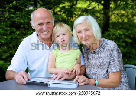 Happy smiling grandparents relaxing outdoors in the garden watching with their granddaughter photo book, a gift from children as a memory of summer vacation - stock photo