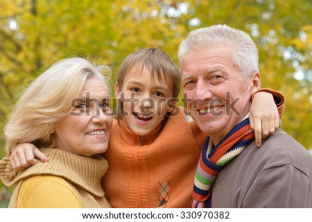 Happy smiling grandparents with their grandson in autumn forest
