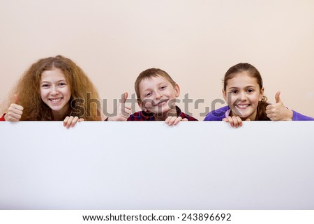 Happy smiling group of kids, friends, boys and girls, showing thumb up and white blank placard, board, poster. - stock photo