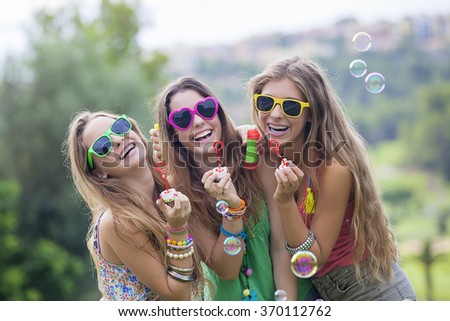 happy smiling group of teen girls blowing bubbles - stock photo