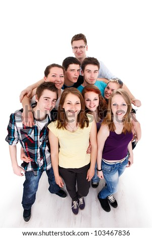 Happy smiling group of young friends standing and embracing together, top view - stock photo