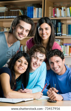Happy smiling group of young students working together in a college library - stock photo