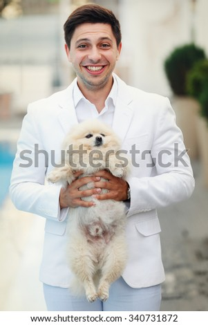 Happy smiling handsome groom in white suit holding dog near pool - stock photo