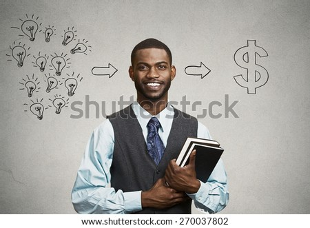 Happy, smiling handsome man holding books has ideas ready for financial success isolated black grey wall background. Positive human facial expression dynamism. Education economics concept - stock photo