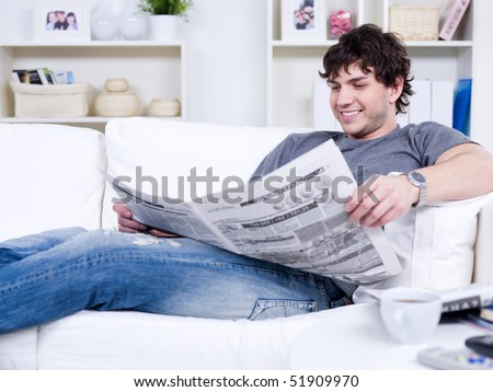 Happy smiling handsome man reading newspaper at home - stock photo