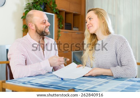 Happy smiling husband and wife signing a contract and buying apartment - stock photo