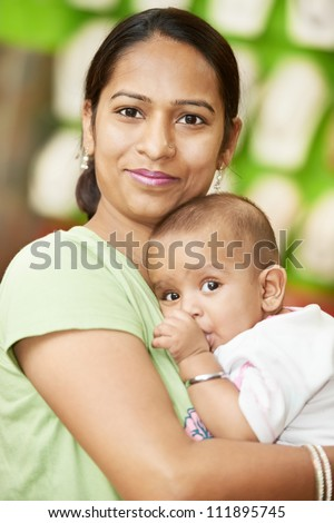 Happy smiling Indian woman mother hugging her little child boy