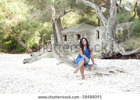 happy smiling indian woman sitting on the beach. - stock photo