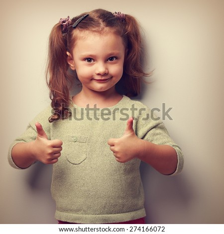 Happy smiling kid girl showing two hands thumb up. Vintage closeup portrait - stock photo