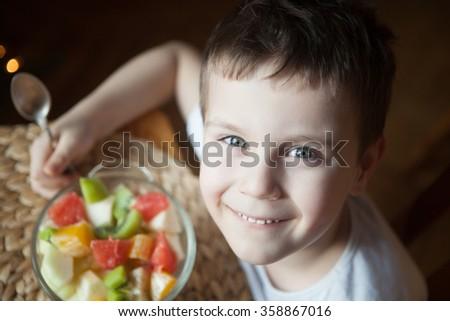 Happy smiling kid holding a large bowl of fruit salad - stock photo