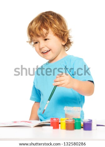 Happy smiling kid painting with paintbrush and smiling - stock photo