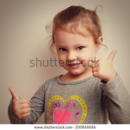 Happy smiling kid with two thumbs up. Closeup vintage portrait - stock photo