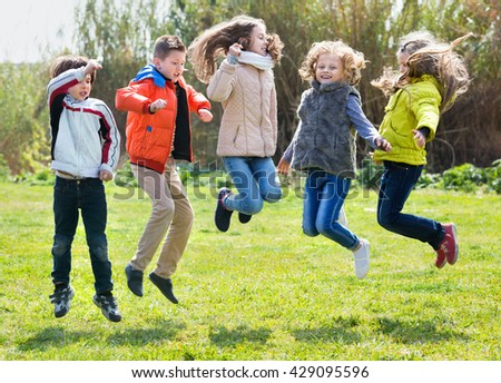 Happy smiling kids having fun and jumping up in spring field - stock photo