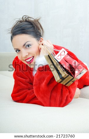 Happy smiling lady laying on a sofa with gift packages - stock photo