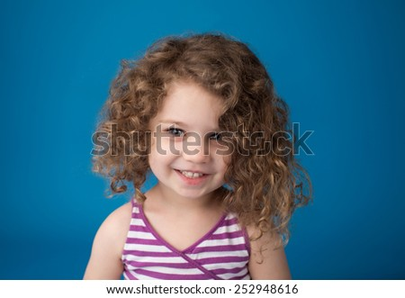 Happy smiling laughing child looking at camera: girl with curly hair