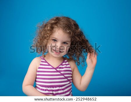 Happy smiling laughing child looking at camera: girl with curly hair  - stock photo