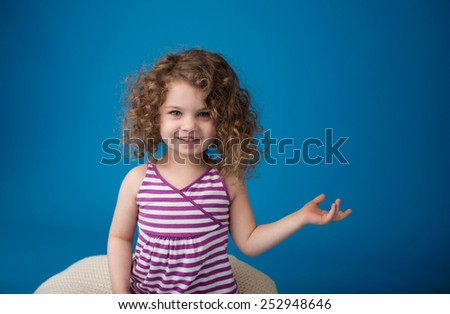 Happy smiling laughing child looking at camera: girl with curly hair holding something or pointing at something - stock photo