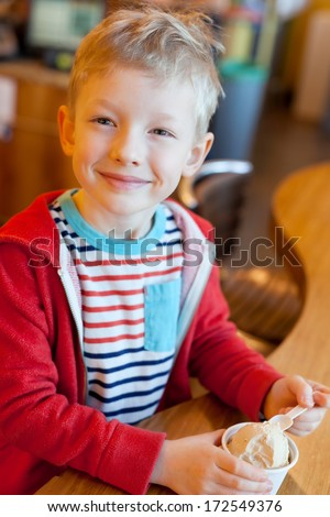 happy smiling little boy eating ice cream in cafe - stock photo