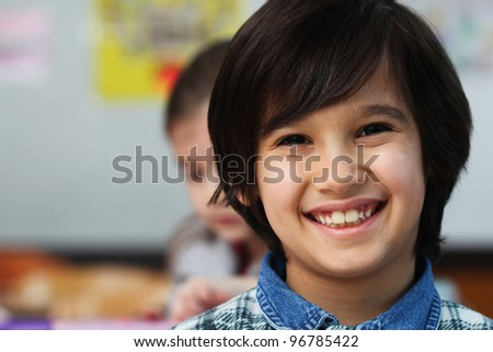 Happy smiling little boy in classroom - stock photo