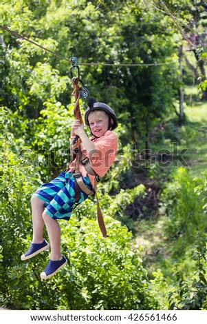 Happy smiling little boy riding a zip line in a lush tropical forest