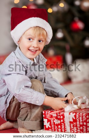 Happy smiling little boy unwrapping a Xmas gift as he kneels bare foot on the floor in front of the Christmas tree in his festive red Santa hat - stock photo